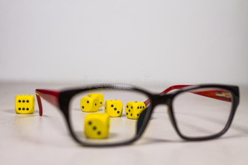 Six Yellow Dice on Clean Gray White Background Behind Glasses royalty free stock image