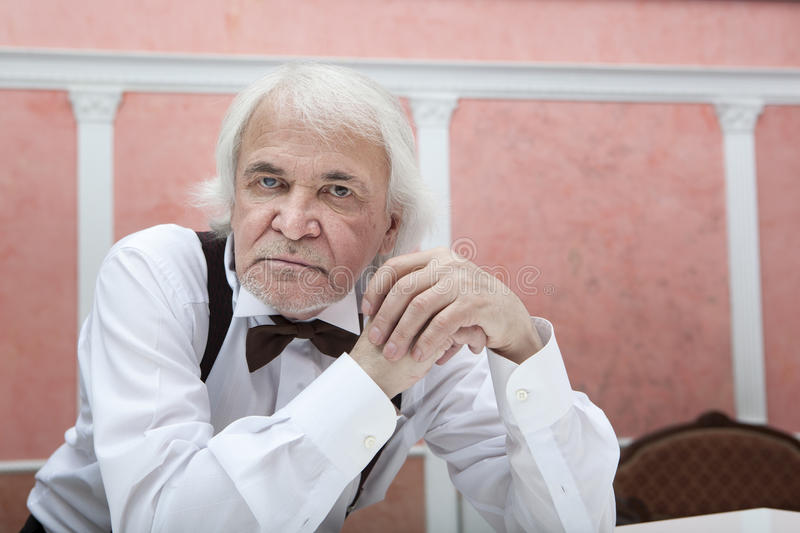 Sixty years gray-haired man in a white shirt and bow tie royalty free stock photography