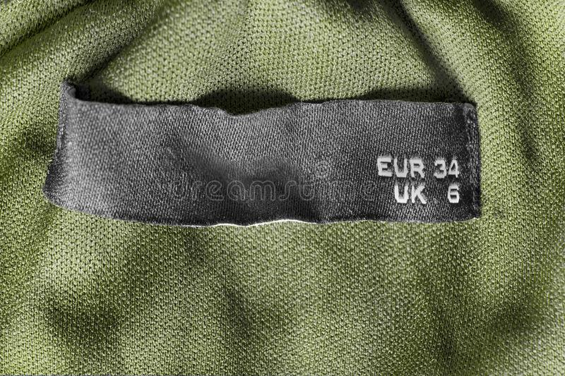 34 size clothes label. On khaki green textile background closeup royalty free stock images
