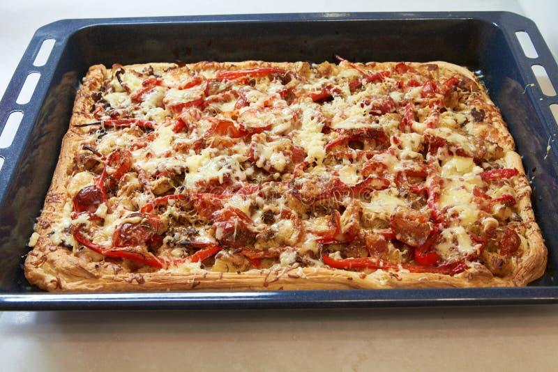Sizilianische rechteckige Pizza mit Käse- und Tomatenbelag auf Backblech stockfotos