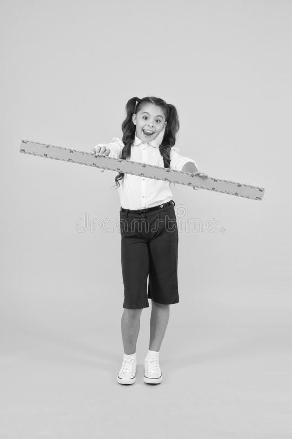Sizing and measuring. School student study geometry. Tell me about distance. Kid school uniform hold ruler. Pupil cute royalty free stock images