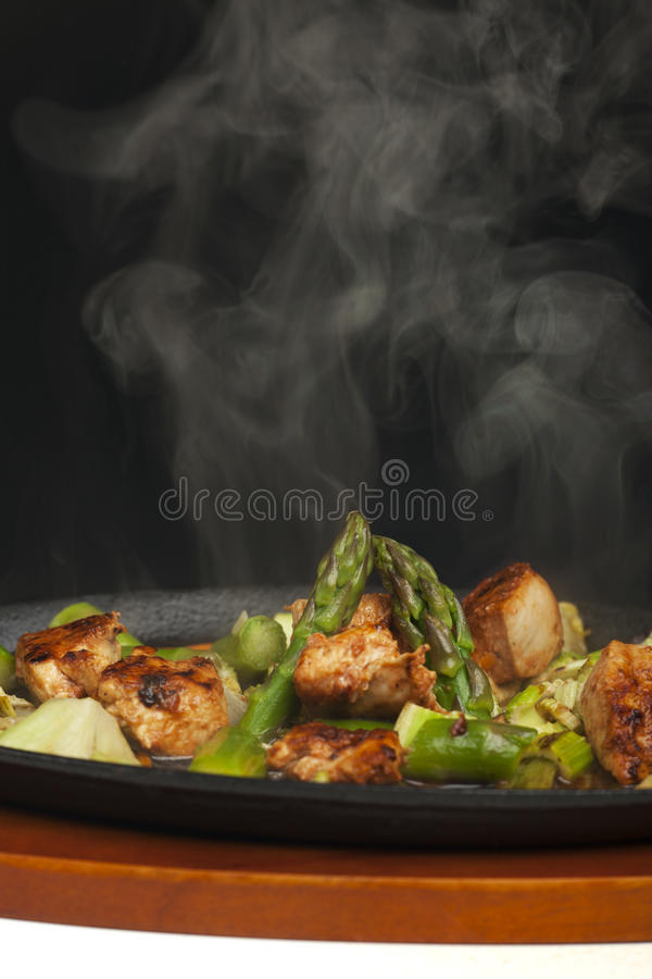 Sizzler. Chicken meat with asparagus in a sizzler stock photography