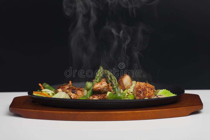 Sizzler. Chicken meat with asparagus in a sizzler stock photo