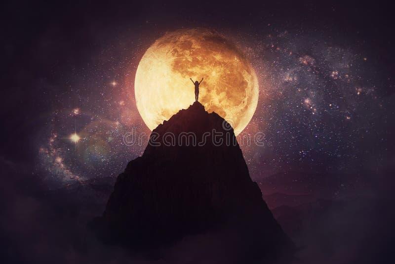 Självövervinnande koncept som en person som höjer upp och ner på toppen av ett berg över nattens fullmåne Övervinnande av hinder royaltyfria bilder