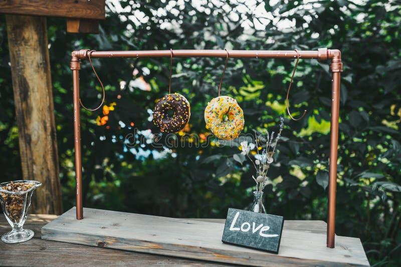 Själv-gjorda kakor som hänger på krokar i godisstång i sommarträdgård royaltyfria bilder
