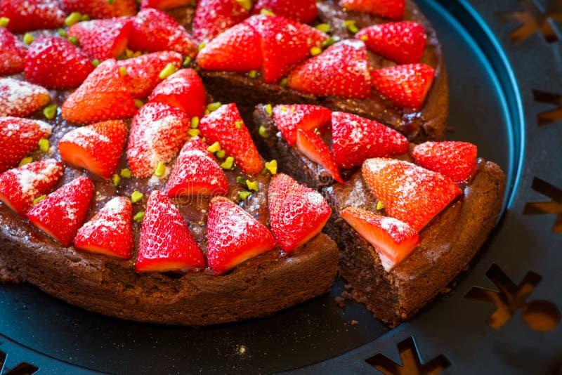 Själven gjorde stycket av den nya bakade jordgubbechokladkakan fotografering för bildbyråer