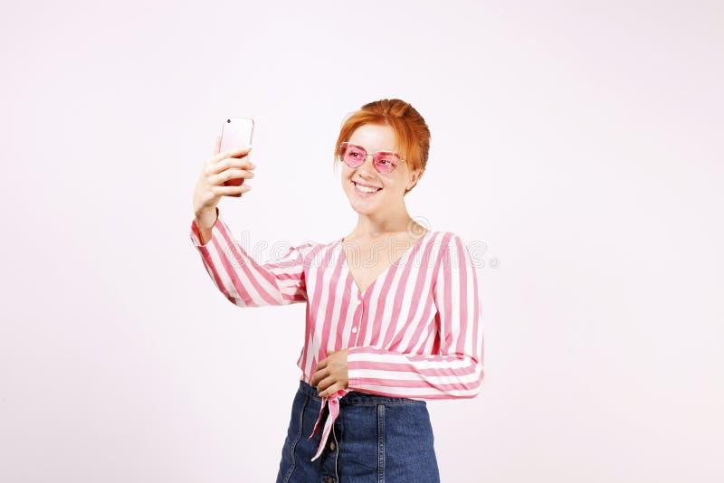 Själven hemsökte den roliga unga härliga kvinnan med naturligt rött hår, bärande rosa solglasögon för kattöga & den avrivna fnure arkivfoto