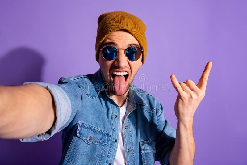 Självfoto av en glad galen rockfläkt som visar ett stenmärke med fingrar som håller tungan fri och bär jeans denim arkivfoton