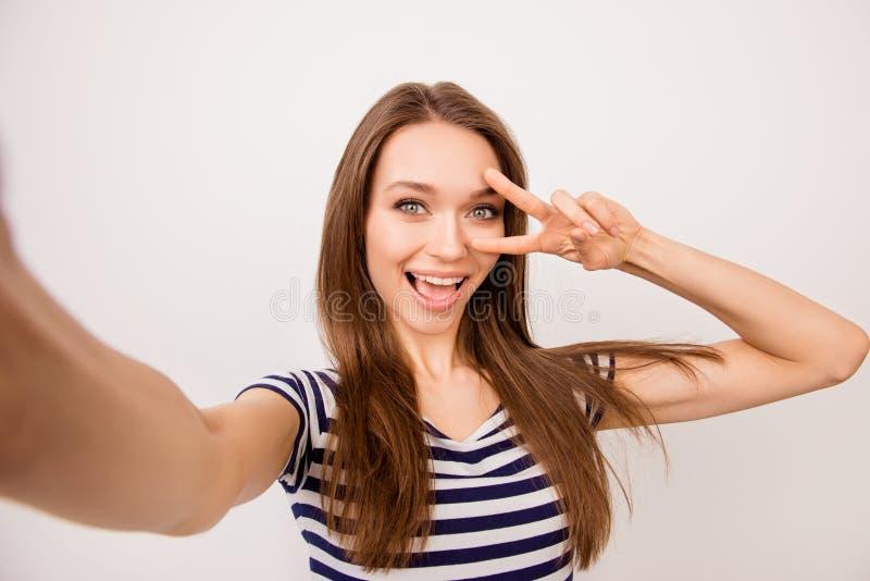 Självporträtt av den nätta skratta drömma flickan i randig t-shir royaltyfria bilder