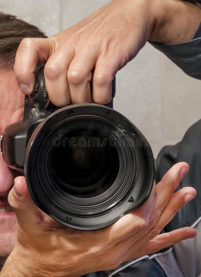 Självporträtt av händerna i spegeln som rymmer en SLR kamera royaltyfria bilder