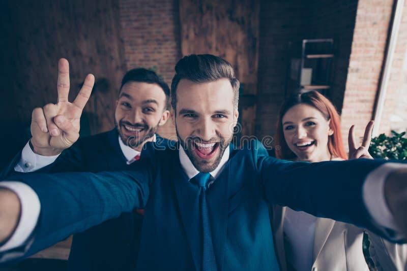 Självporträttet av tre trevliga stilfulla härliga stiliga gladlynta galna optimistiska utövande chefer som visar v-tecknet, tycke arkivbild