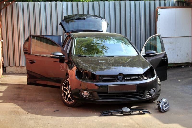 Självreparation av en bil på sommar, nära garage Ändrande billyktor Svart hatcback utan det främre billyktor och gallret av eleme royaltyfri bild