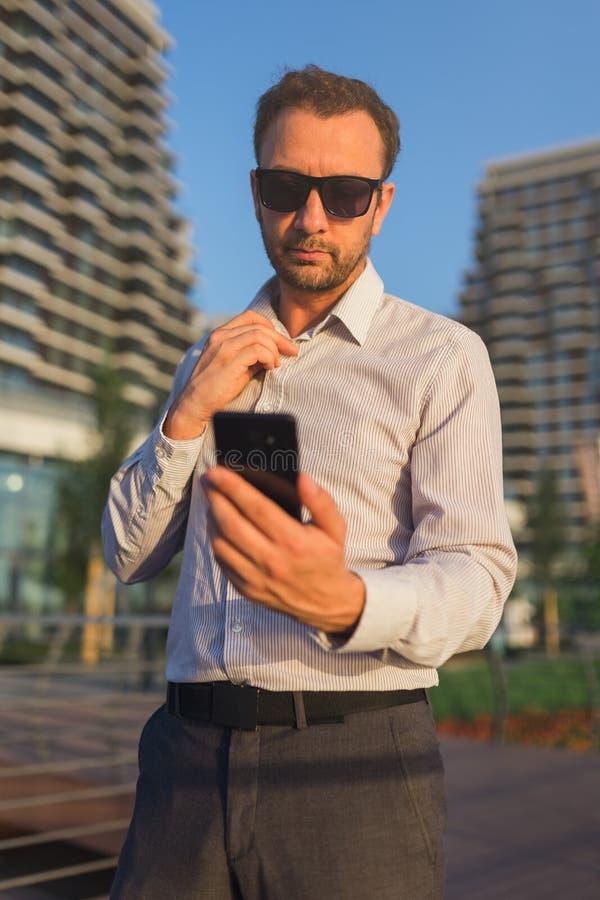 Självsäker affärsman som framme använder smartphonen av kontorsbyggnad arkivbild