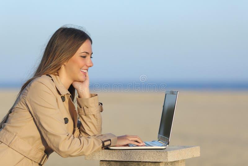 Självständig kvinna som utomhus arbetar med en bärbar dator royaltyfri foto