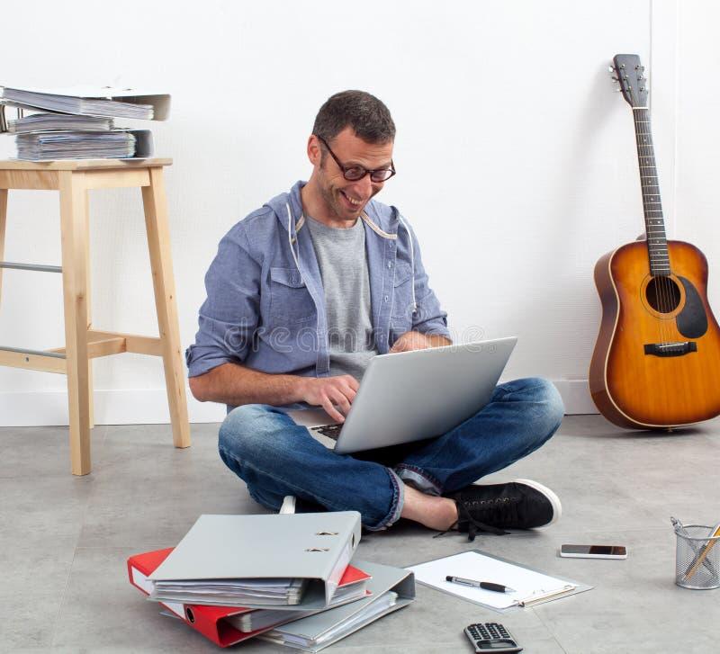 Självständig man som arbetar hans budget på datoren royaltyfri foto