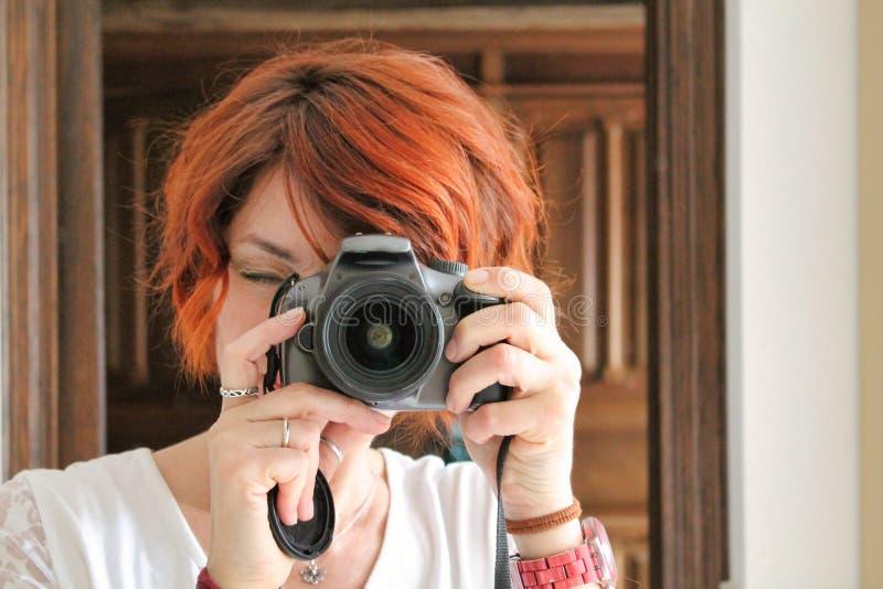 Självstående av den kvinnliga fotografen med kopparaktigt hår royaltyfri fotografi