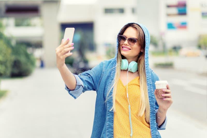 Självstående av den lyckliga härliga moderna trendiga unga kvinnan som dricker kaffe på stadsgatan royaltyfri fotografi