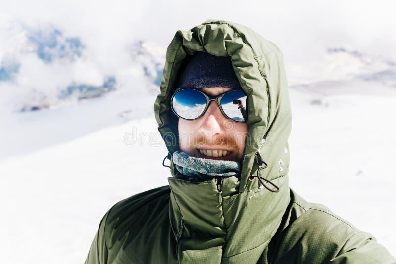 Självstående av en lycklig grabb i vinter i bergen, når att ha klättrat arkivfoton