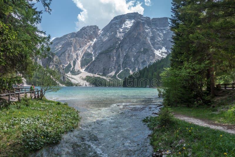 Sjö Braies med livliga färger i vår med berg i bakgrunden i norden av Italien fotografering för bildbyråer