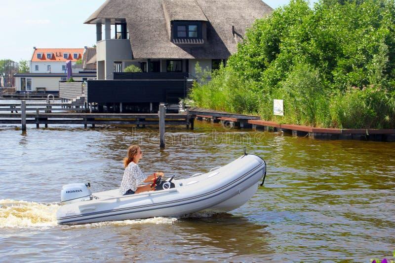 Sjö för rörelse för motoriskt fartyg för ung kvinna, Loosdrecht, Nederländerna royaltyfri foto
