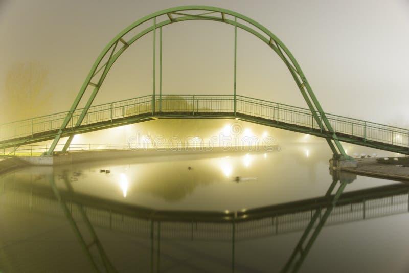 Sjö med en bro på en dimmig natt royaltyfria bilder