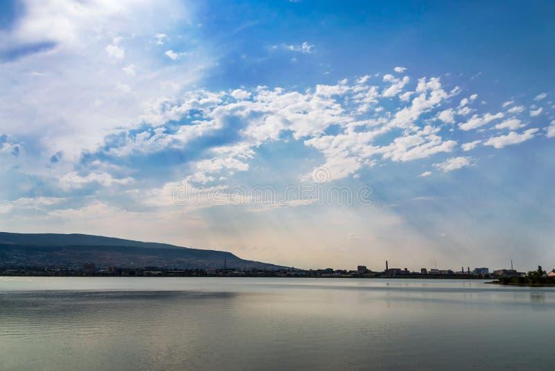 Sjö med spegeln som vatten- och solljusbortgång till och med molnen arkivbild