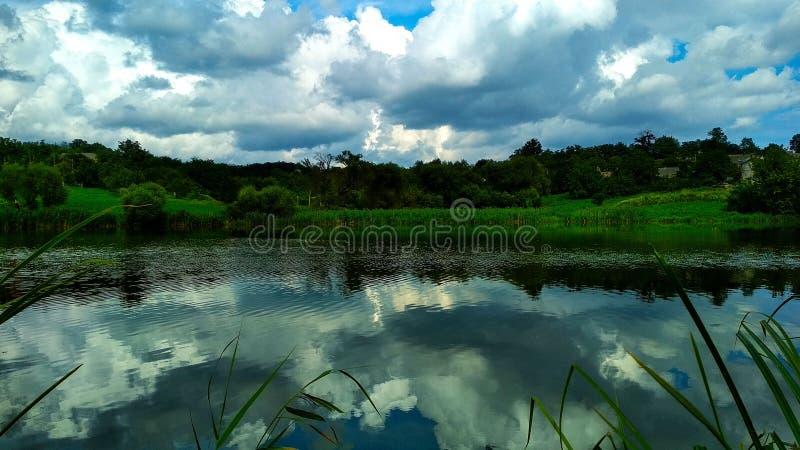 Sjö med träd i bakgrunden och en reflexion av himlen i vattnet royaltyfria foton