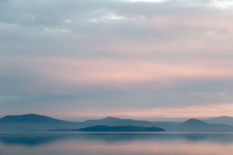 Sjö på skymning, med härliga varma signaler i himlen och vatten royaltyfri fotografi
