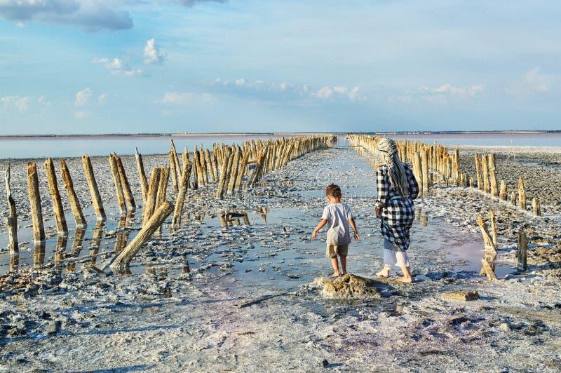 Sjö Sasyk-Sivash, Krim En kvinna och ett barn går på sjön, med deras baksidor till kameran Gränsmärke turister, lopp royaltyfri bild