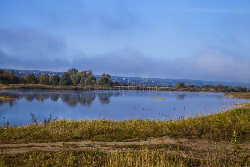 Sjö tidigt på morgonen med en dimma arkivbild
