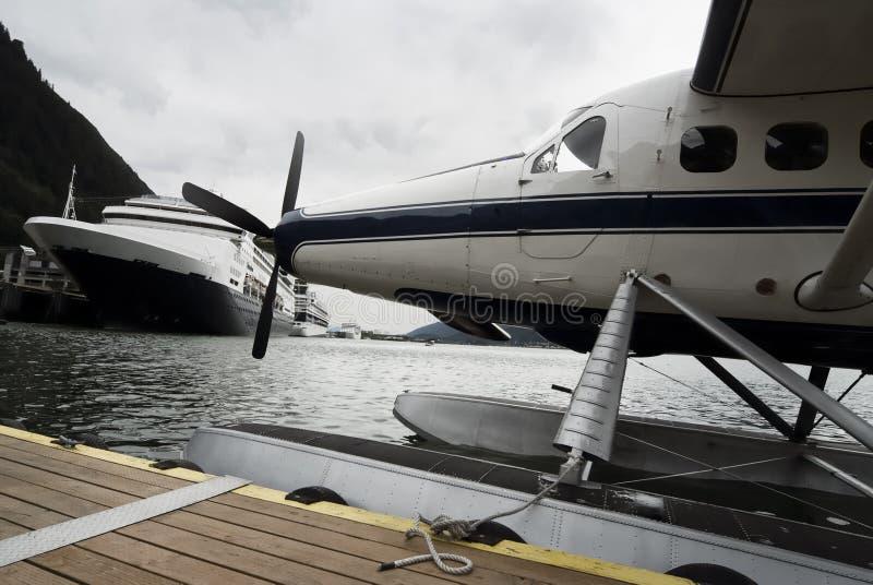 Sjöflygplan- och kryssningskepp anslöt längs pir i Alaska royaltyfri bild