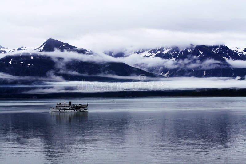 Sjögående skepp i ett molnigt berglandskap arkivbild