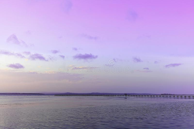 Sjölandskap med bryggan vid violett himmel på solnedgången royaltyfria foton