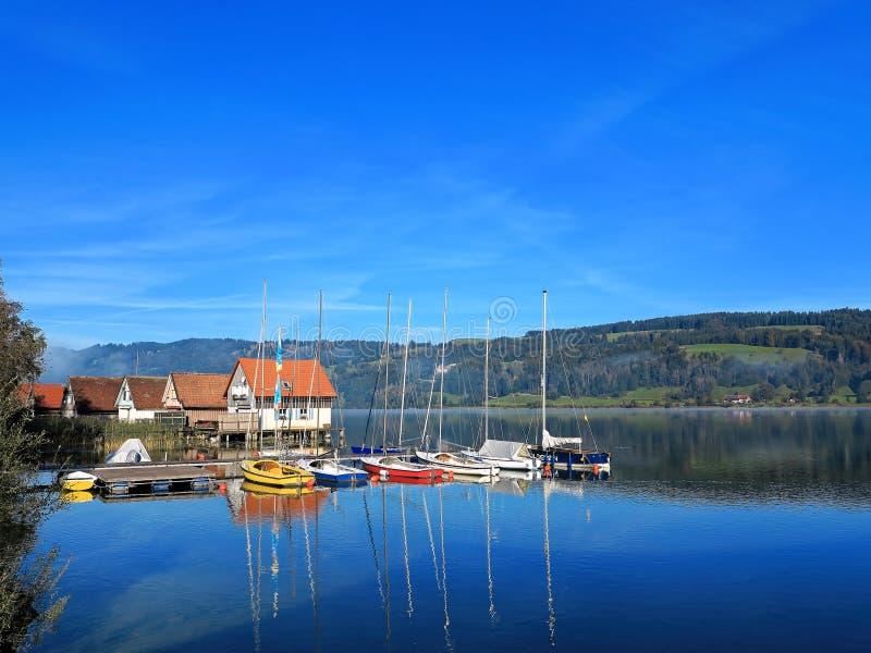 Sjölandskap med moderna styltahus och segelbåtar arkivfoto