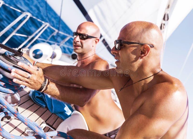 Sjömän som arbetar på segelbåten royaltyfri fotografi