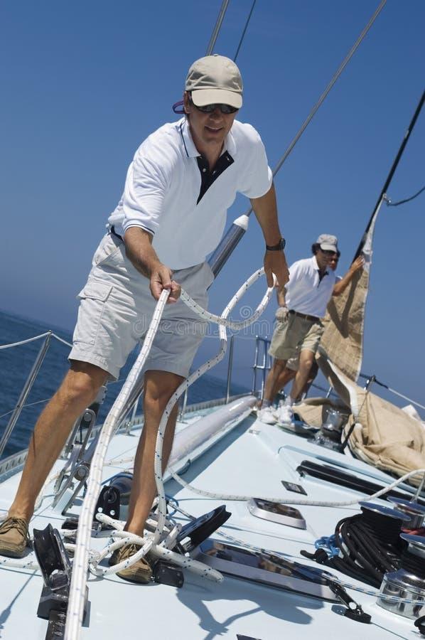 Sjömän som arbetar rep på yachtdäck royaltyfri foto
