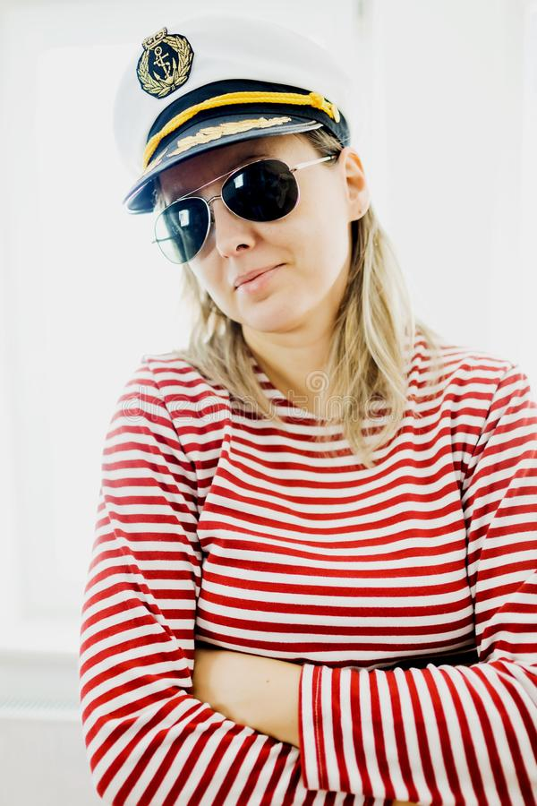Sjöman för Sceptically ung kvinna i kaptenlock - bärande röda mellanrum klär arkivfoto