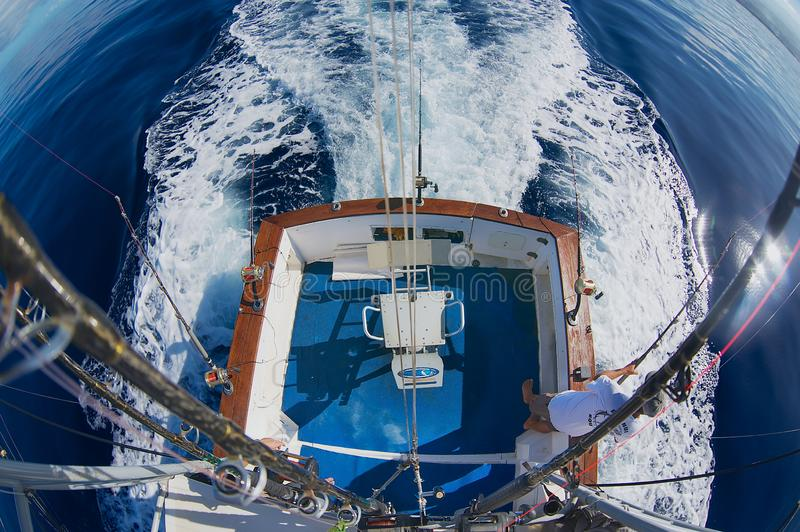Sjömannen får klara rullar och stänger för modigt fiske för marlin på havet nära Saint Denis, Reunion Island arkivbild