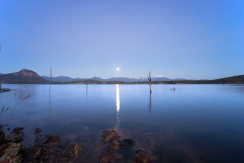 SjöMoogerah Australien soluppgång med fullmånen arkivbilder