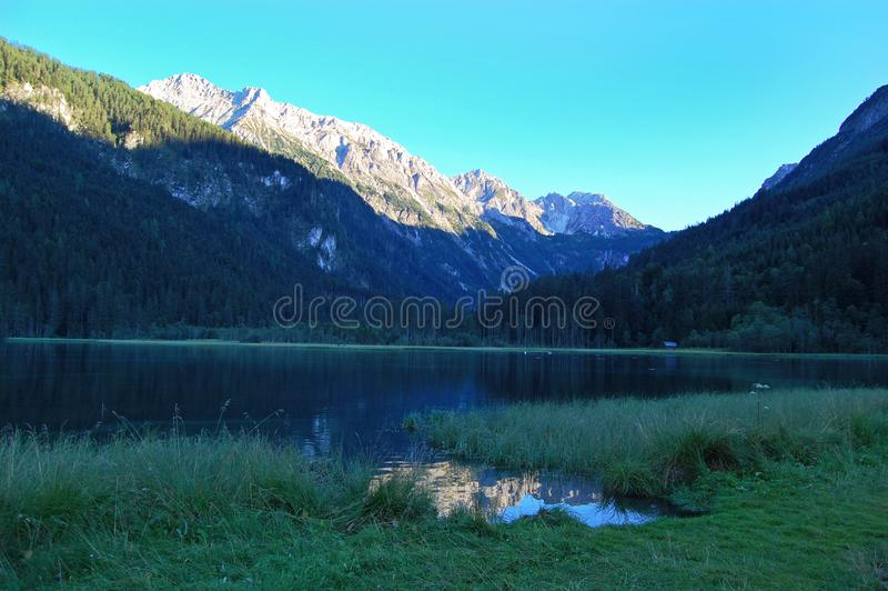 Sjön i bergen, skönhet av naturen, det alpina landskapet, berg, blå himmel, snö täckte bergmaxima royaltyfri foto