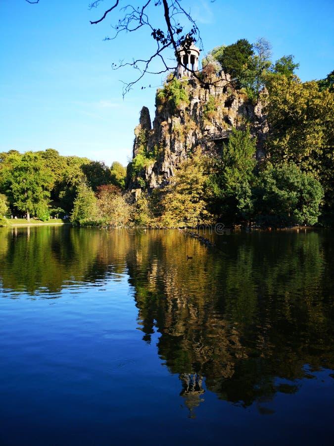 Sjön och berget i Buttes Chaumont parkerar i Paris royaltyfri foto