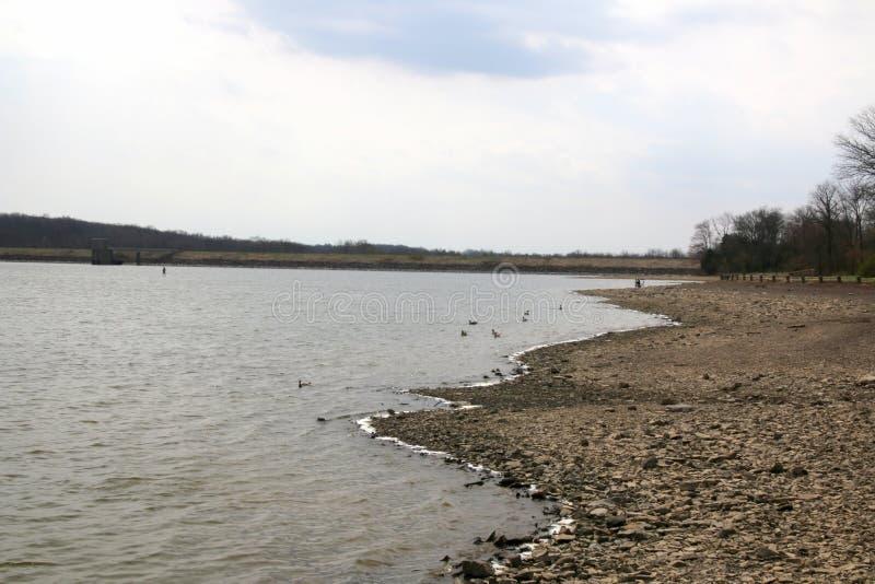 Sjön på en vårdag med vaggar på kusten arkivbild