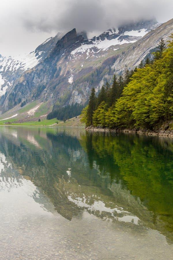 Sjön Seealpsee, reflekterade det snowcapped berget, moln fotografering för bildbyråer