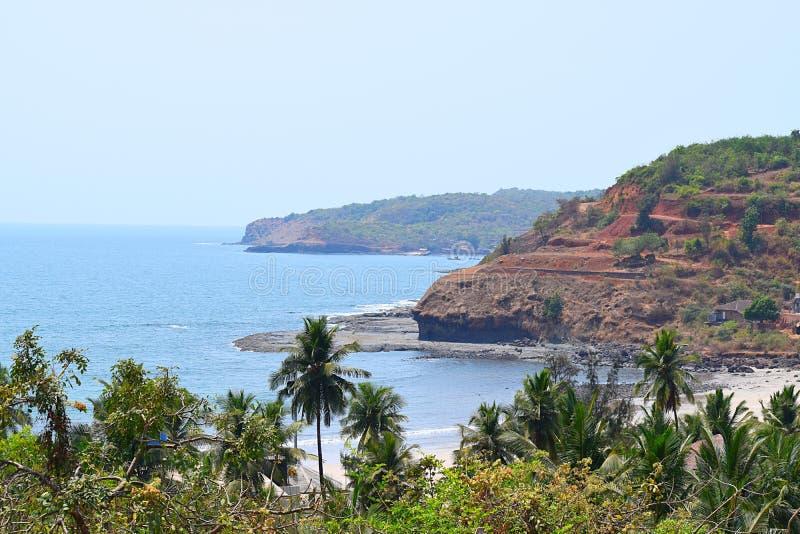 Sjösida av Arabian Sea med kullar och palmträd, Velaneshwar strand, Ratnagiri, Maharashtra, Indien - en naturlig bakgrund royaltyfria bilder