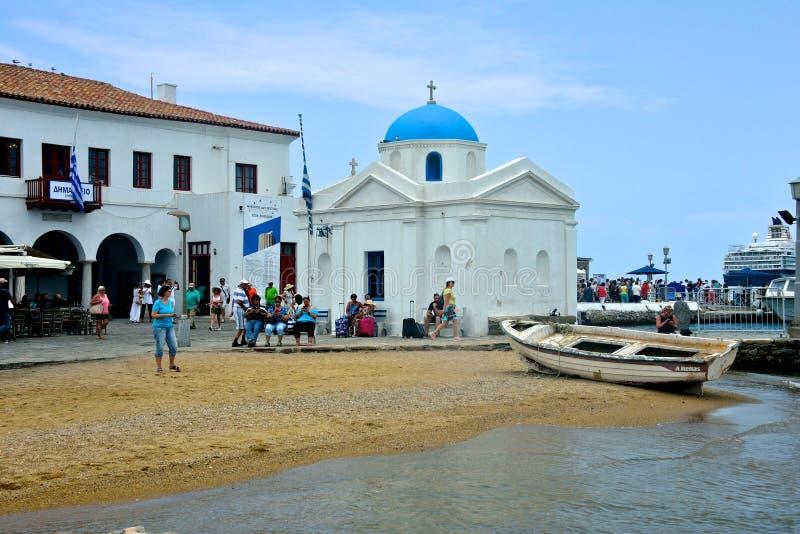 Sjösida av Chora med en typisk grekisk kyrka nära stranden och mycket turist som framme kopplar av av havet arkivbild