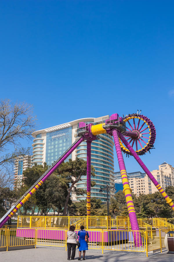 Sjösidaboulevard, Baku, Azerbajdzjan - April 9, 2017 Ungdomarsom rider en karusell under ferien royaltyfri fotografi