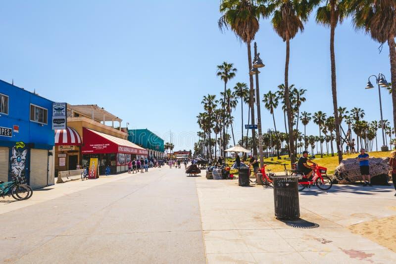 Sjösidapromenad med shoppar och palmträd arkivfoto