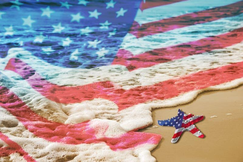 Sjöstjärna med USA flaggan på den sandiga stranden för begrepp för arbets- dag royaltyfria foton