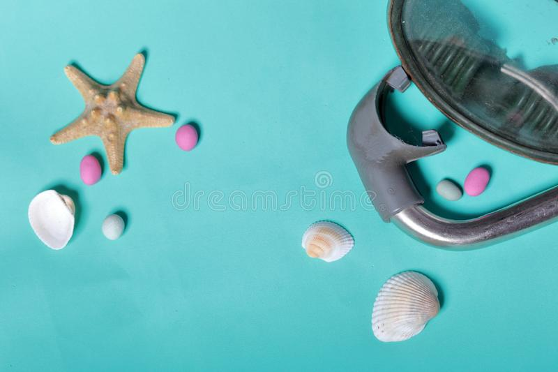 Sjöstjärna, skal och kulöra kiselstenar Maskering med en snorkel för dykapparatdykning De ligger på ett grovt linnetyg royaltyfri foto