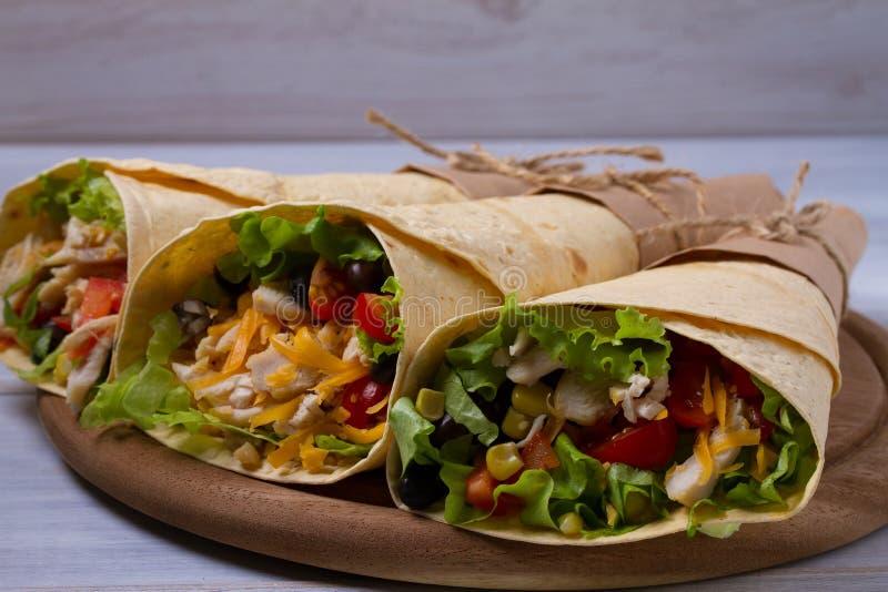 Sjalar med höna, tomater, grönsallat, svarta bönor, cheddarost och majs Tortillan burritos, smörgåsar vred rullar arkivfoton
